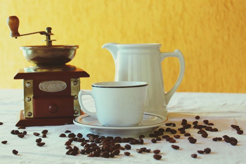 Close-up of coffee cup and grinder on table