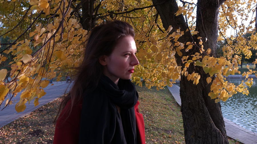 Young woman looking away while standing on tree trunk during autumn