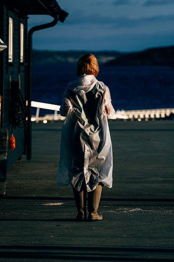 Rear view of woman walking on sea against sky