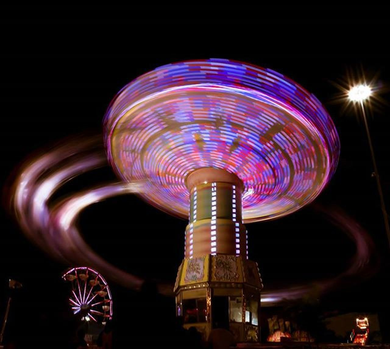 amusement park, night, arts culture and entertainment, amusement park ride, ferris wheel, illuminated, carousel, fun, enjoyment, traveling carnival, multi colored, blurred motion, long exposure, motion, merry-go-round, leisure activity, sky, low angle view, outdoors, black background, nightlife, no people