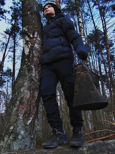 Low angle view of man standing by tree trunk in forest