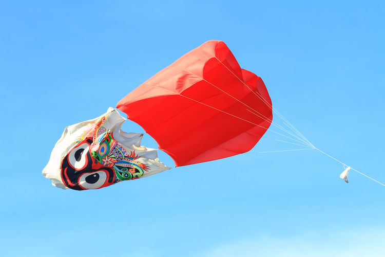 Low angle view of kite flying in blue sky