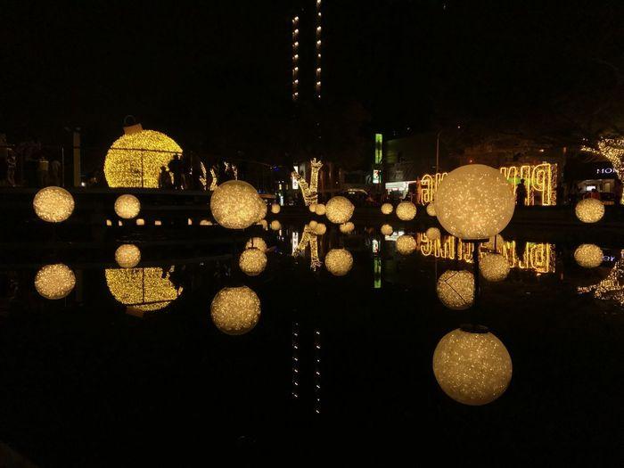 Illuminated lighting equipment hanging in city at night