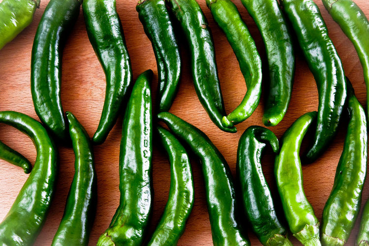 Full frame shot of green chili peppers on table