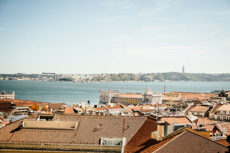 Rooftop View in Lisbon, looking across the city and the river Architecture Portugal Rooftop Sunny Ecity Explore Lisbon Orange And Blue River Roofs Roofs From Above View From Above