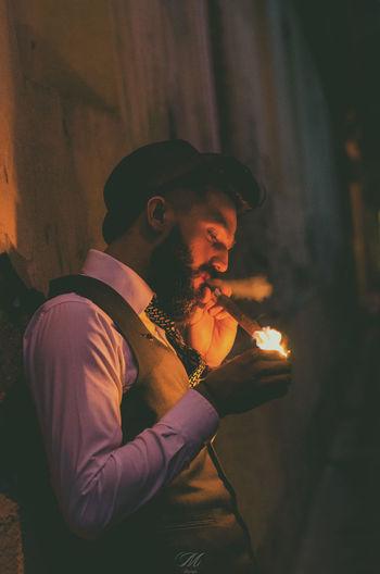 Man smoking cigar while standing by wall at night