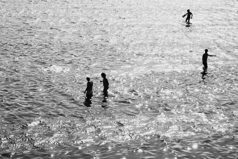 High angle view men in sea during sunny day