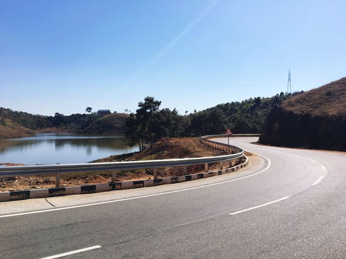 Road by lake against clear blue sky