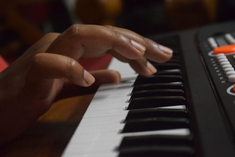 Cropped hand playing piano in darkroom