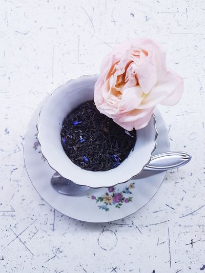 Close-up of black tea leaves in cup and rose on table