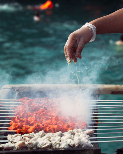 Human Hand Hand Preparation  Human Body Part Heat - Temperature Smoke - Physical Structure Food And Drink Holding Food Barbecue Grill Burning Barbecue People Meat Freshness Focus On Foreground Day Preparing Food Grilled Outdoors Finger Kebab