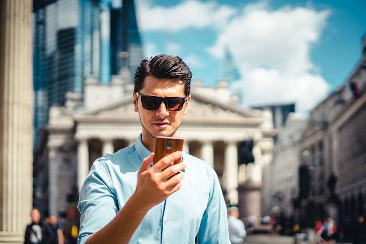 Portrait of young man wearing sunglasses standing in city