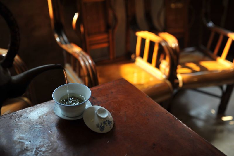 Cropped pot pouring tea in cup on table