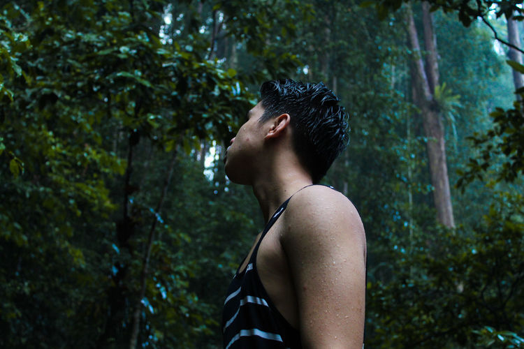 Side View Of Young Man Standing In Forest During Rainy Season