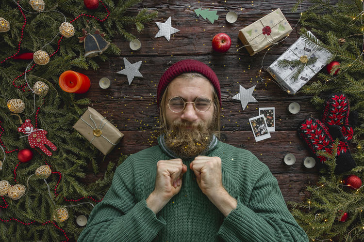 Christmas portrait of a man looks like a Santa Christmas Celebration Decoration Christmas Decoration One Person Holiday christmas tree Portrait Christmas Ornament Beard Looking At Camera Facial Hair Indoors  Adult Directly Above Headshot