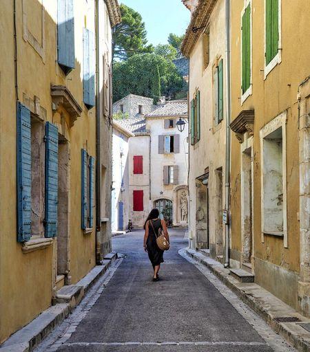 Rear view of woman walking on street amidst buildings in city
