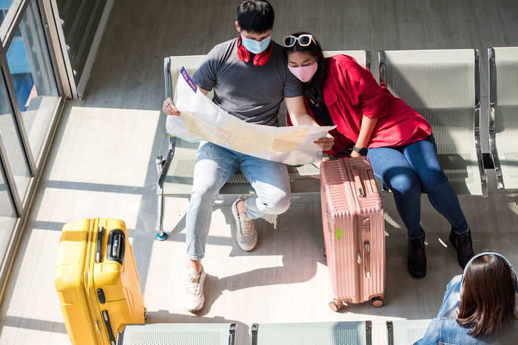 High angle view of couple sitting at airport