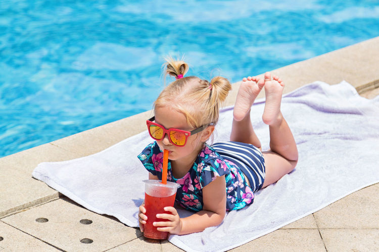 High angle view of cute boy drinking water in swimming pool