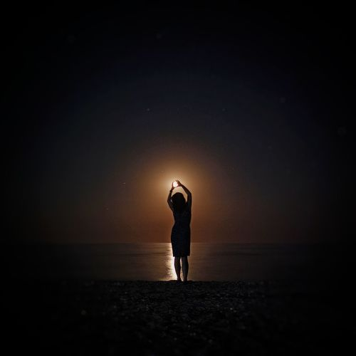 Silhouette man standing on beach against sky at night