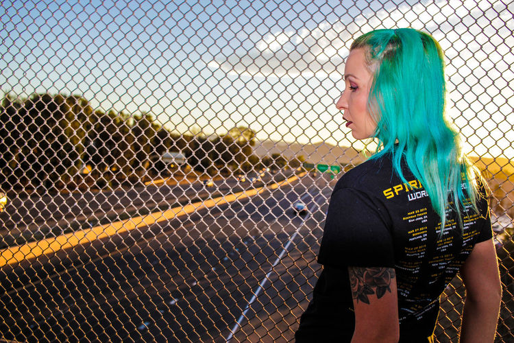 Woman Standing Next To Chainlink Fence