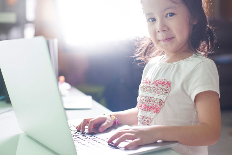 Portrait of smiling cute girl using laptop at home