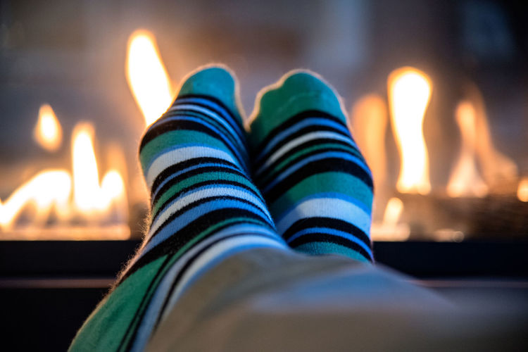 Low section of person wearing socks against fireplace at home