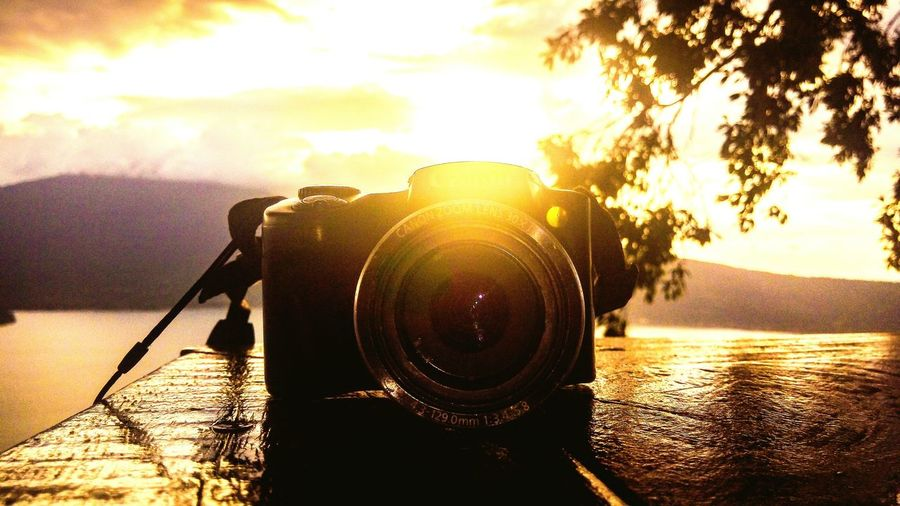 Close-up of camera with reflection in lake against sunset sky