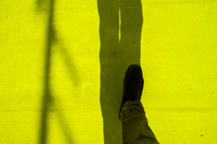 Low section of man walking on yellow floor
