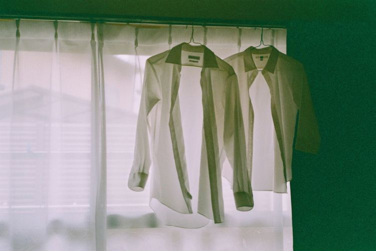 Shirts hanging against window at home