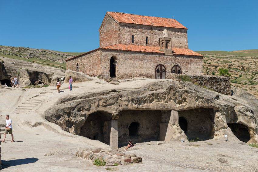 GEORGIA. UPLISTSIKHE CAVE TOWN - JUNE 13, 2017: Tourists walks through the cave city. The oldest stone church is built in the highest point of the city. Ancient Antique Archeology Church Georgia Lost Ruins Uplistsikhe Ancient Civilization Architecture Building Exterior Cave City Cave Town Civilization Clear Sky History Leisure Activity Old Ruin Outdoors People Rocks Stone Sunlight Temple Tourism