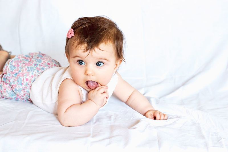 baby girl with tongue out Tongue Out Hair Toddler  Lying On Front Fashion Baby Girl Hairclip Child Childhood Bed Baby Young Portrait Innocence Lying Down Cute Front View One Person Real People Babyhood