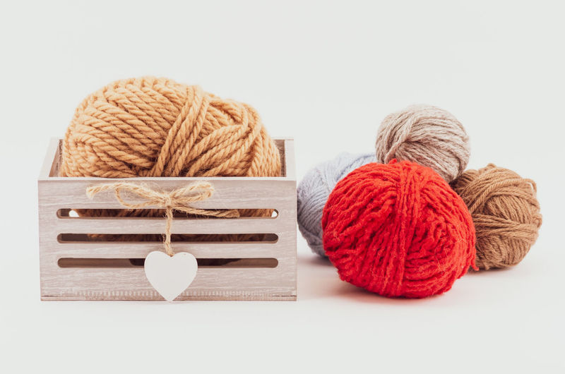 woolen clews Wool Material Ball Of Wool Art And Craft Still Life Craft Studio Shot Indoors  White Background Textile Knitting Knitting Needle Creativity Multi Colored Thread Close-up Table Copy Space Sphere Warm Clothing Scarf Wood Basket