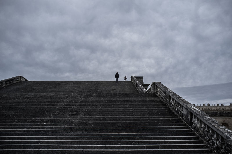 Low Angle View Of Father And Son Moving Down On Staircase Against Cloudy Sky