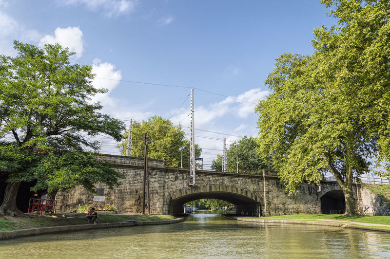 Canal du midi in Carcassonne Arch Arch Bridge Arched Architecture Bridge Bridge - Man Made Structure Built Structure Canada Canal Du Midi Carcassonne Cloud Cloud - Sky Connection Day Engineering Long No People Outdoors Power Line  Sky The Way Forward Town Transportation Tree Water