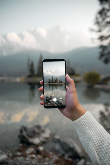 Cropped hand of woman photographing with mobile phone against lake