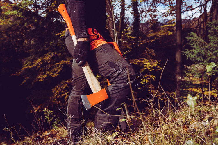 Woodcutter man with axe and chainsaw - the woodcutter serie