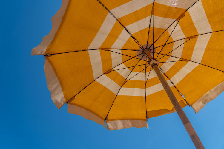 Low angle view of yellow umbrella against clear blue sky