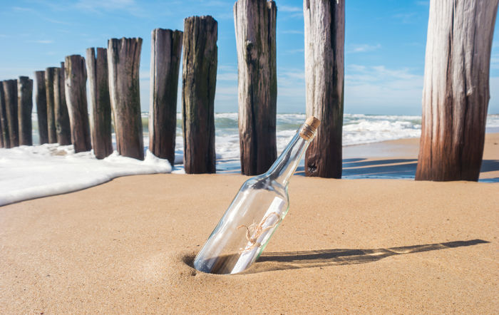 Message in a bottle at the beach Cork Froth Shadows & Lights Aground Beach Beauty In Nature Bottle Bottle Beach Breakwater Close-up Communication Day Groyne Message Message In A Bottle Nature No People Outdoors Sand Sea Sky Summer Water Waves Waves, Ocean, Nature