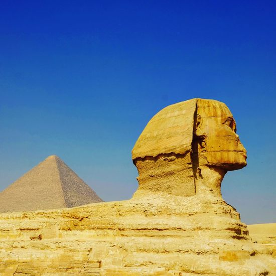 the great sphynx and khofu's pyramid Tourism Tourism Destination Sphynx Pyramid Desert History Ancient The Past Sand Travel Destinations Ancient Civilization Architecture Old Ruin Arid Climate Clear Sky Blue Archaeology Outdoors Triangle Shape Day Built Structure No People Nature