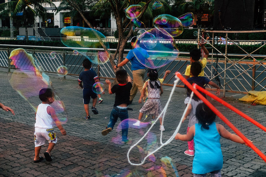 Multi Colored Real People Fun Enjoyment Outdoors Lifestyles Leisure Activity Men Day Playing Full Length Togetherness Large Group Of People Architecture Bubble Wand Adult People Adults Only Eyeem Philippines The Street Photographer - 2017 EyeEm Awards Street Photography Street Photo Streetphoto_color Layering Urban Lifestyle Color