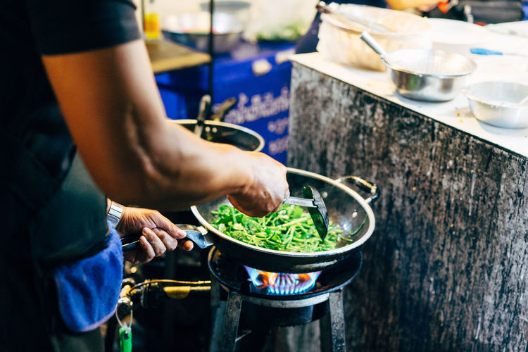 Man cooking fresh vegetables in a wok