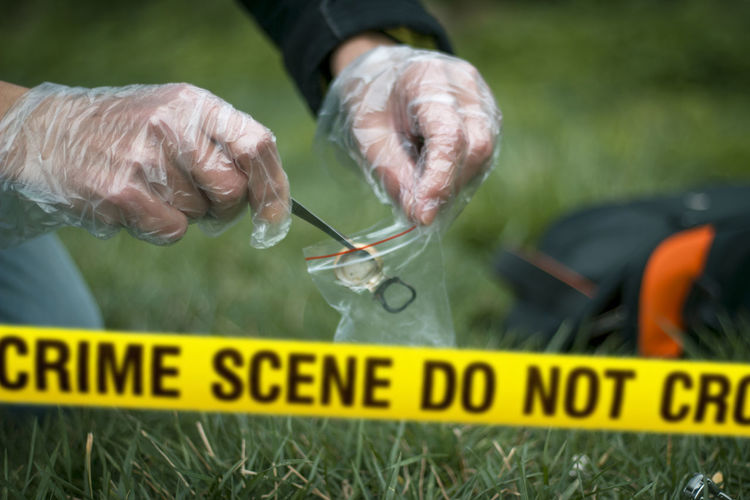 Cropped hands collecting evidence at crime scene