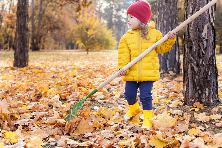 Cute kid standing with broom by trees during autumn