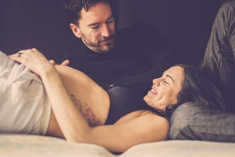 Man Relaxing By Pregnant Woman On Bed At Home