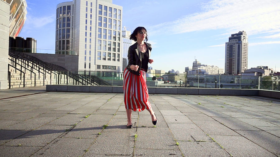 Happy woman wearing striped skirt and jacket on footpath in city