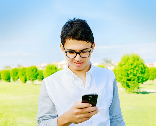Young Man Using Smart Phone Outdoors
