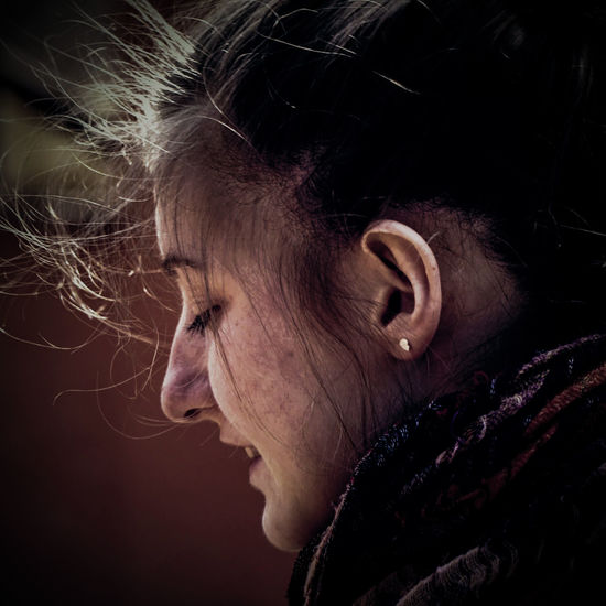 Close-up side view of young woman with messy hair outdoors