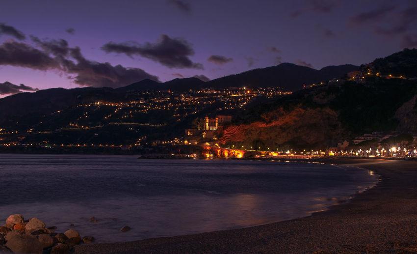 Illuminated beach by sea against sky at night