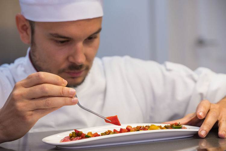 Close-up of chef garnishing food in plate on table