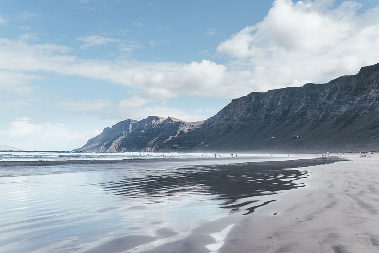 Reflections in wet sand at playa de famara beach on lanzarote against mountains and sky